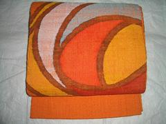 ざっくり紡がれた柿色紬の帯